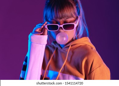 Pretty young 20s fashion teen girl model wear stylish glasses hoodie blowing bubble gum standing at purple violet studio wall background, igen teenager in trendy night party glow 80s 90s concept