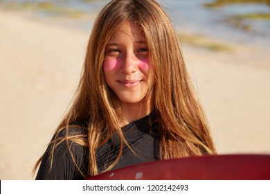 Pretty young active woman with long hair, has pink protective mask for surfing, uses surf zinc which is not easy to wash off and blocks suns ultraviolet rays, needs safe surfboarding, poses outdoor