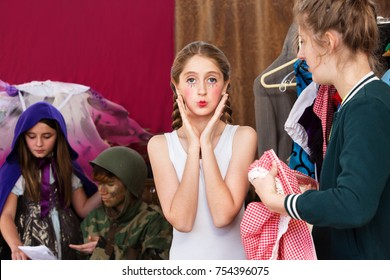 Pretty young actress pouts at the camera as other students prepare for their parts