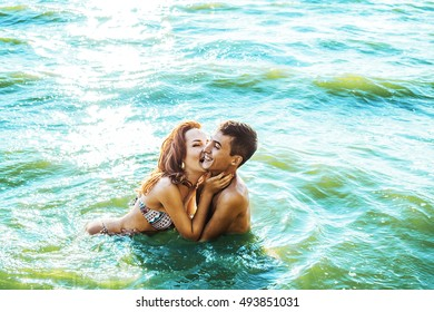 pretty young adult couple embracing, kissing and sitting on bottom in blue hot sea against water texture. Hand caressing the girl's neck and biting Man