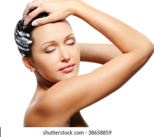 Pretty young adult woman washing her head with shampoo