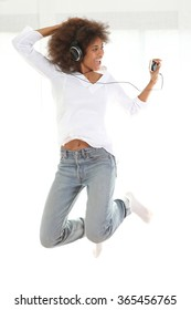 Pretty young african american girl listening music from her mobile phone and jumping. Standing against white background.