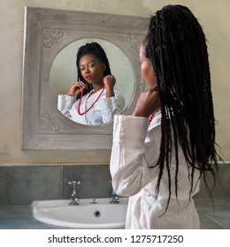Pretty young african american woman doing her morning routine in front of the bathroom mirror