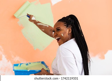 Pretty young african american woman with painting roller indoors. Redecoration, renovation, apartment repair and refreshment concept.