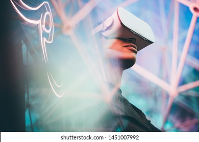 Pretty young African girl adjusting the VR headset on the modern background.