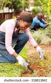pretty young african girl gardening with her husband on background