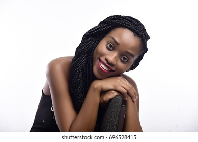 Pretty young African girl sitting on a office chair, smiling.