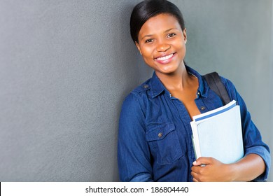 pretty young african university girl standing against the wall