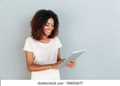 Pretty young afro american woman standing and using tablet computer isolated over white background