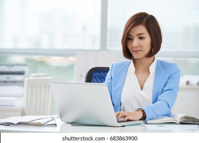 Pretty young Asian business woman working on computer in her office