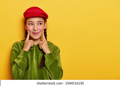 Pretty young Asian model keeps both fore fingers on cheeks, looks with dreamy expression aside, has minimal makeup, wears red beret, green velvet hoody, poses over yellow wall with blank space