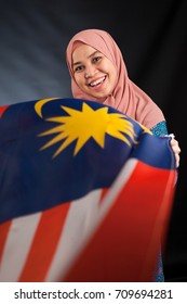 Pretty young Asian Muslim woman posses with a flag of the malaysia beautiful in action. Islamic fashionable attire concept!