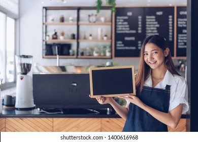 Pretty young asian waitress standing arms crossed in cafeteria.Coffee Business owner Concept.  barista in apron smiling at camera in coffee shop counter