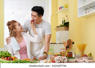Pretty young Asian woman feeding boyfriend with cherry tomato when they are cooking dinner together