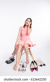 Pretty young asian woman having difficult choice to try on a few pairs of high heels