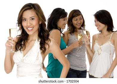 A pretty young asian woman raises a glass of champagne with three friends talking in background