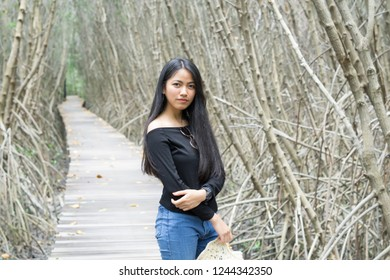 Pretty young asian woman relaxing on the wooden bridge in mangroves forest