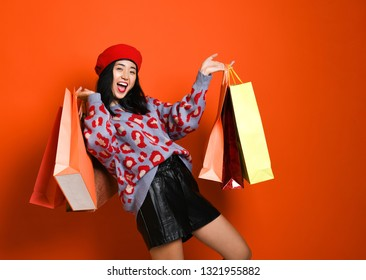 pretty young asian woman stylishly dressed in a red hat beret with bags after shopping isolated on orange studio shot