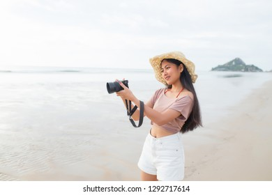 Pretty young asian woman taking photo on the tropical beach