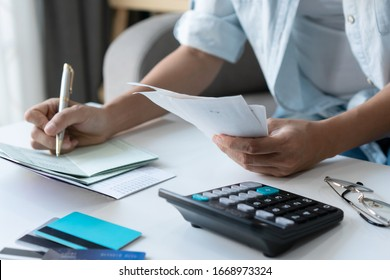 Pretty young Asian woman using a pen writing on bank account book while holding the bills to calculate in living room at home. Expenses, account, taxes, home budget concept.