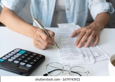 Pretty young Asian woman using a pen wriiting on the bills to calculate home expenses and taxes in living room at home.