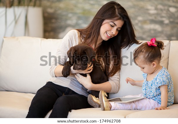 Pretty young babysitter looking after a puppy and a little girl