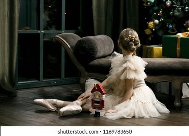 Pretty young ballerina in beautiful tutu with nutcracker in studio, dark background, vintage atmosphere