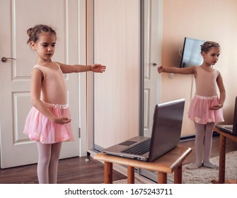 Pretty young ballerina practicing classic choreography during online class in ballet school, social distance during quarantine, self-isolation, online education concept
