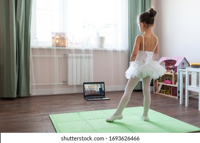 Pretty young ballerina practicing classic choreography during online class in ballet school, social distance during quarantine, self-isolation, online education concept - Shutterstock ID 1693626466