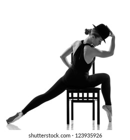 pretty young ballerina sitting on the chair. Isolated on white
