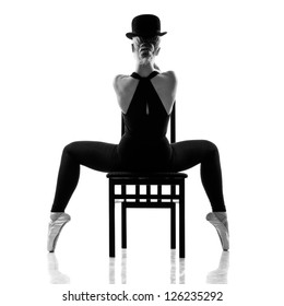pretty young ballerina sitting on the chair. Rear view. Isolated on white