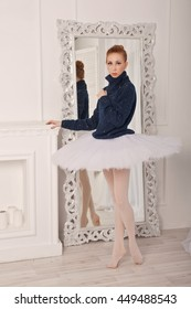Pretty young ballerina standing in front of a mirror. A girl wearing a tutu and a black sweater.