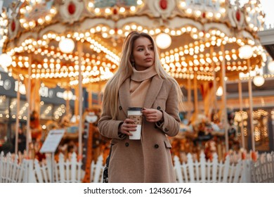 Pretty young beautiful woman in a stylish autumn coat and vintage knitted sweater drinking coffee in a city park against the background of magical bright lights. Fashion elegant girl blond