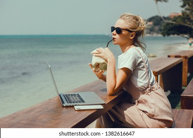 Pretty Young Beauty Woman Using Laptop in cafe, outdoor portrait business woman, hipster style, internet, smartphone, office, Bali Indonesia, holding, mac OS, manager, freelancer, drinking coconut