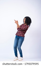 pretty young black lady pointing and facing sideways feeling excited and happy