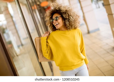 Pretty young black woman with curly hair in shopping