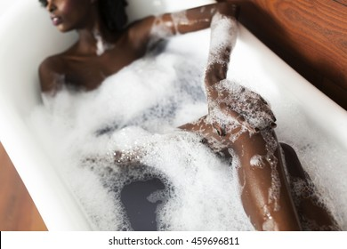 Pretty young black woman in the foam bath