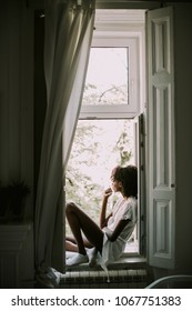 Pretty young black woman sitting on the window in room and smoking cigarette