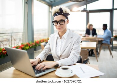 Pretty young blond businesswoman wearing headband, eyeglasses and elegant suit in cafe
