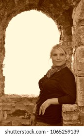 Pretty, young, blond, chubby woman with face piercing and neckerchief leans on a stone wall in front of a window and looks to the side. Sepia.