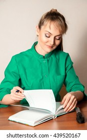 Pretty young blond doctor in green gown making a notes. Health and medical concept