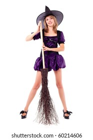 pretty young blond woman dressed as a witch with a broom