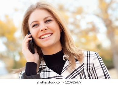Pretty Young Blond Woman on Her Cell Phone Outside on Fall Day.