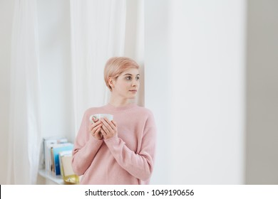 Pretty young blond woman relaxing with coffee standing leaning against a wall indoors looking back out of a curtained window