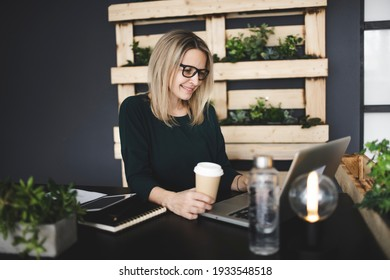 pretty, young and blond woman with stylish, modern black glasses sits in a sustainable office and enjoys a coffee to go