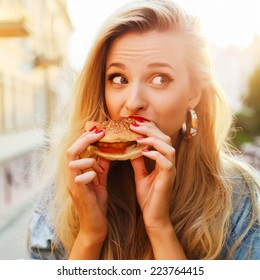 Pretty young blonde funny woman eating hamburger outdoor on the street