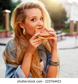 Pretty young blonde funny woman eating hamburger outdoor on the street with red lipstick on lips