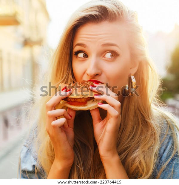 街でハンバーガーを食べている、かわいい若い金髪のおかしな女性