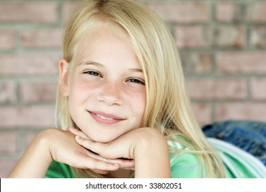 A pretty young blonde haired girl posing with hands under chin, shallow depth of field with focus on face, horizontal with copy space