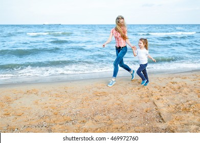 Pretty young blonde mother and little cute girl run and laugh at the beach. Travel and Vacations.